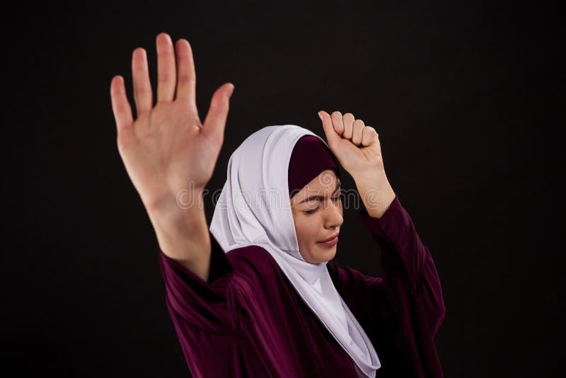 Arabische erschrockene Frau im hijab verteidigt sich stockfoto