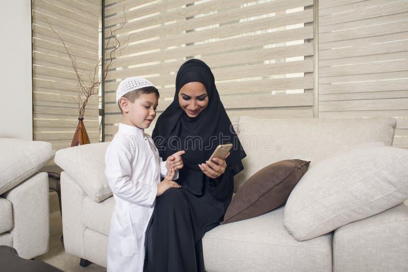 Arabische familie, Arabische moeder en zoon die mobiele telefoon met behulp van royalty-vrije stock fotografie