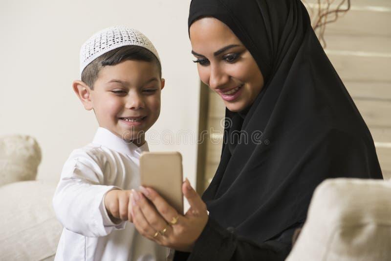 Arabische Familie, arabische Mutter und Sohn, der Handy verwendet stockfoto