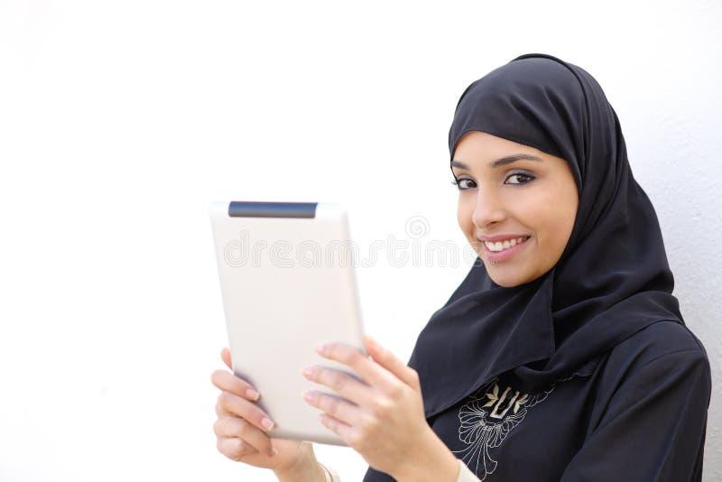 Arabische Frau, die eine Tablette hält und Kamera betrachtet stockbild