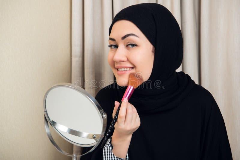 Arabische Frau, die Make-up auf ihrem Gesicht, tragendes traditionelles arabisches Kleid anwendet stockfotos