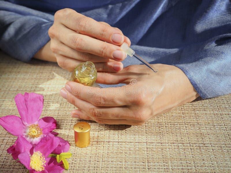 Arabische Frau, die Parfüm auf Handgelenk anwendet lizenzfreie stockbilder