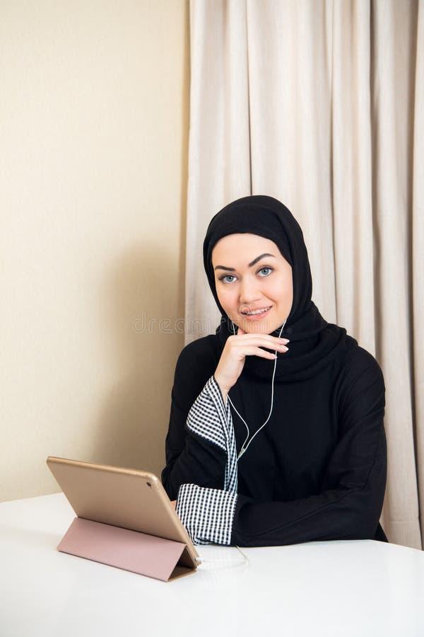 Arabische Frau, die Tabletten-PC-Computer verwendet Südostasiatischer Student zu Hause Lebender Lebensstil der moslemischen Jugen lizenzfreie stockfotos