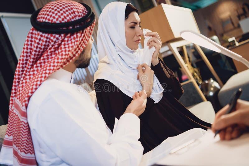 Arabische Frau mit Ehemann an der Psychologeaufnahme stockbild