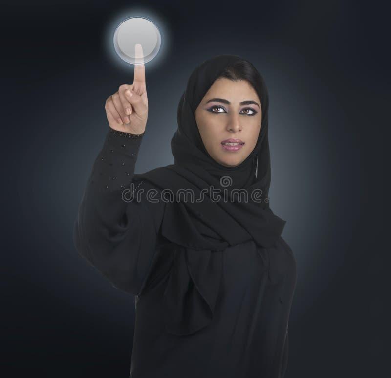Arabische Geschäftsfrau, die ein mit Berührungseingabe Bildschirm bedrängt stockfoto
