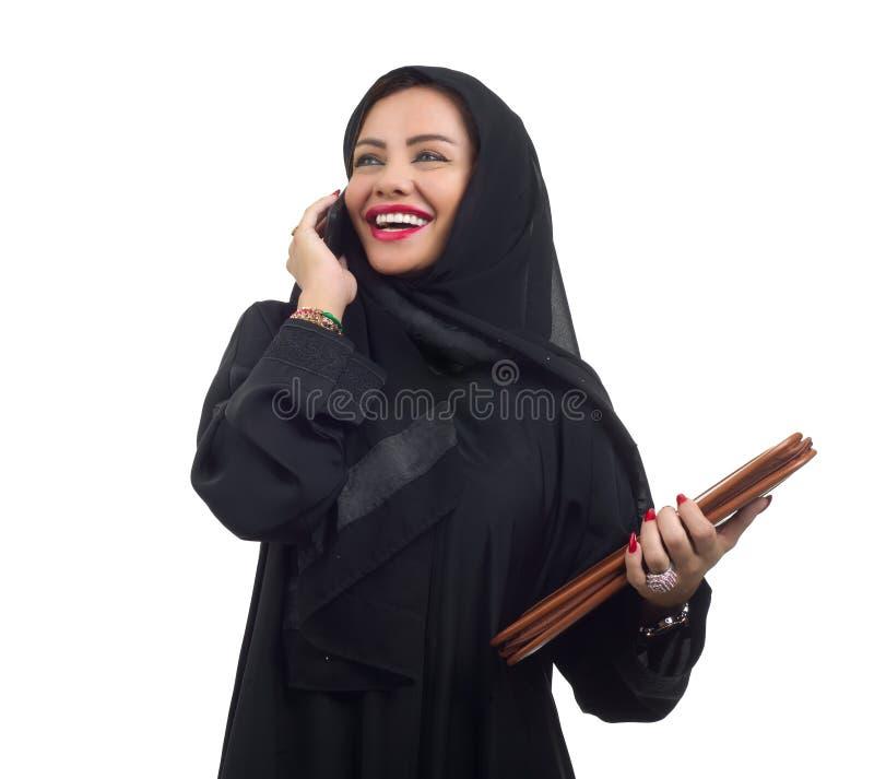 Arabische Geschäftsfrau, die einen Ordner hält und am Telefon lokalisiert auf Weiß spricht stockfotografie