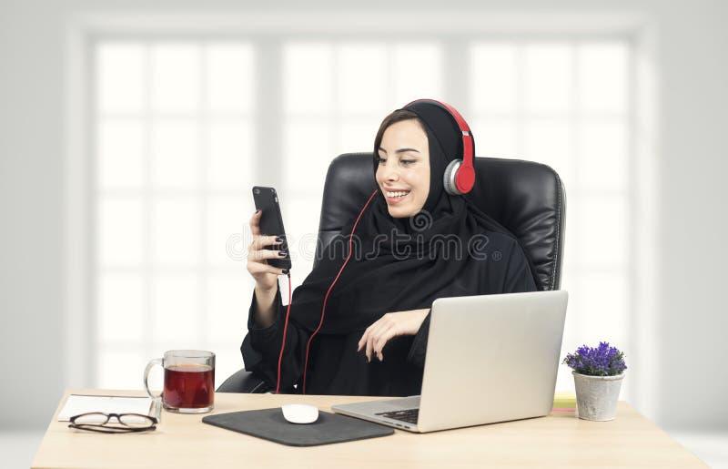 Arabische Geschäftsfrau, die Musik im Büro hört lizenzfreies stockfoto