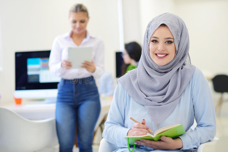 Arabische Geschäftsfrau im Startbüro mit dem Team, das im Hintergrund arbeitet, stockfotos