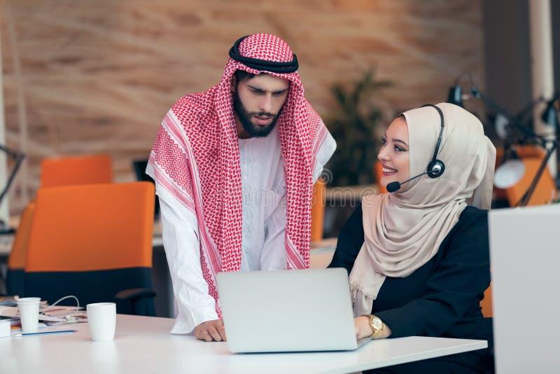 Arabische Geschäftspaare, die zusammen an Projekt im modernen Startbüro arbeiten stockfotografie