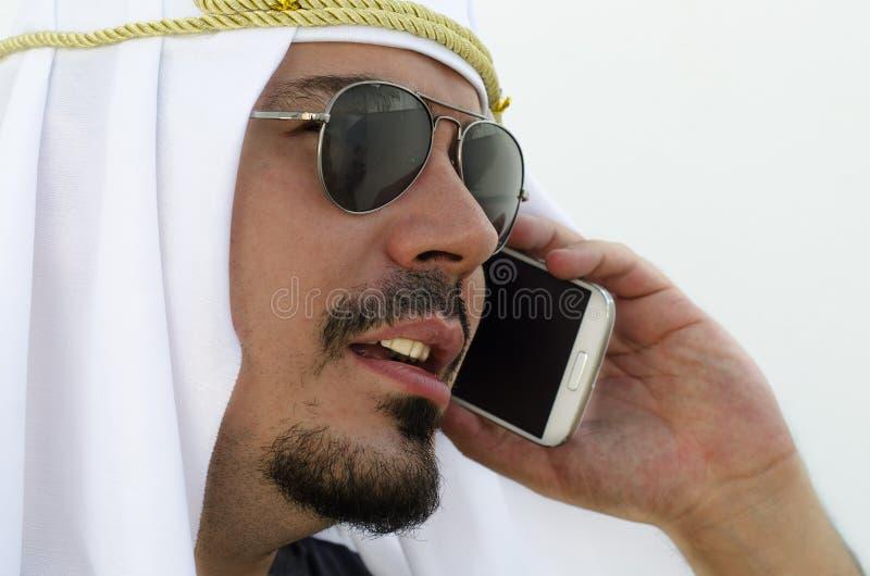 Arabische mens die bij smartphone roepen stock afbeelding