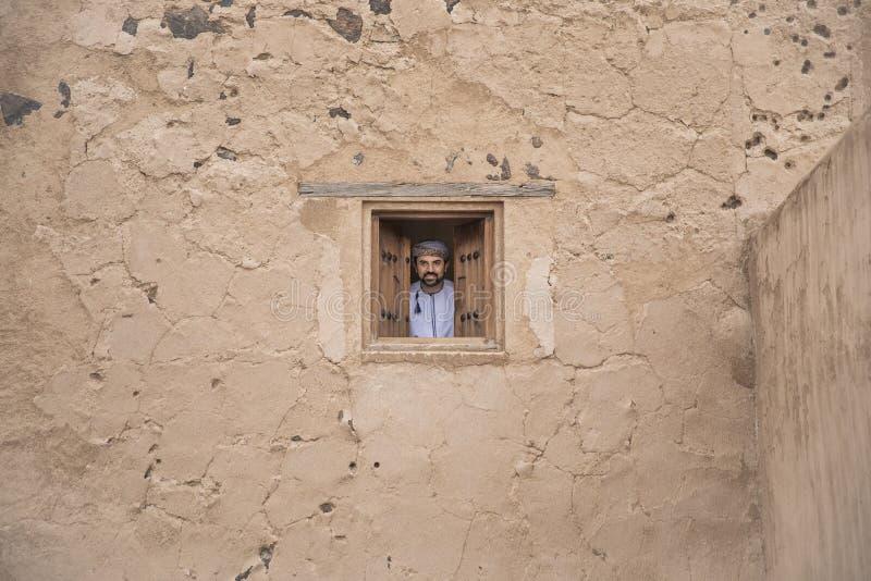 Arabische mens die in traditionele omani uitrusting uit een venster kijken royalty-vrije stock fotografie