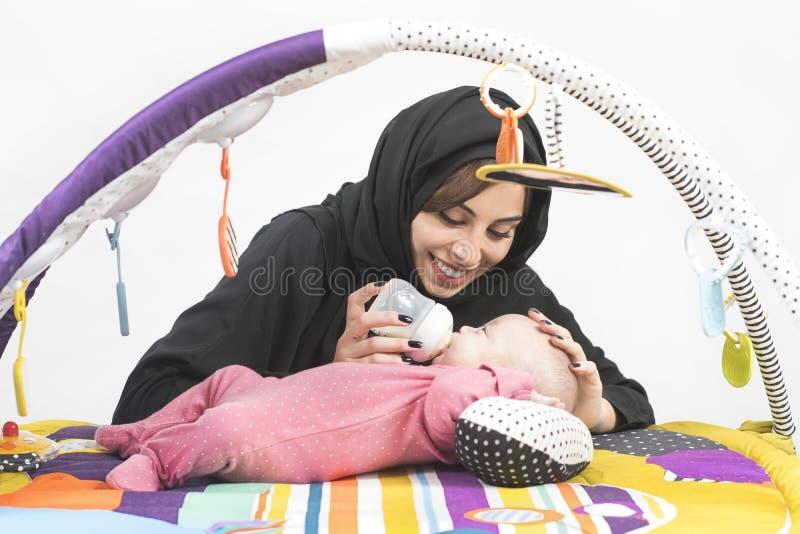 Arabische Moeder die haar babymeisje op een spelmat voeden stock fotografie
