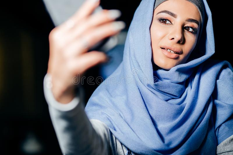 Arabische moslemische Frau, die selfie mit Telefon im Café nimmt stockfotos