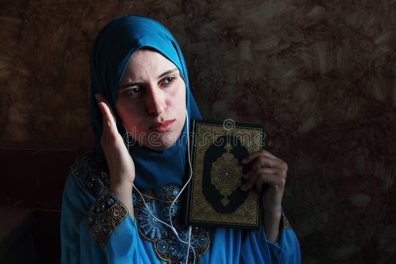 Arabische moslemische Frau mit islamischer Heiliger Schrift und Kopfhörer des Korans stockfotos
