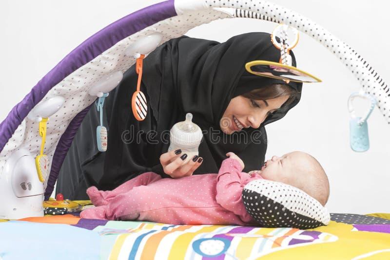 Arabische Mutter, die ihr Baby auf einer Spielmatte einzieht stockbild