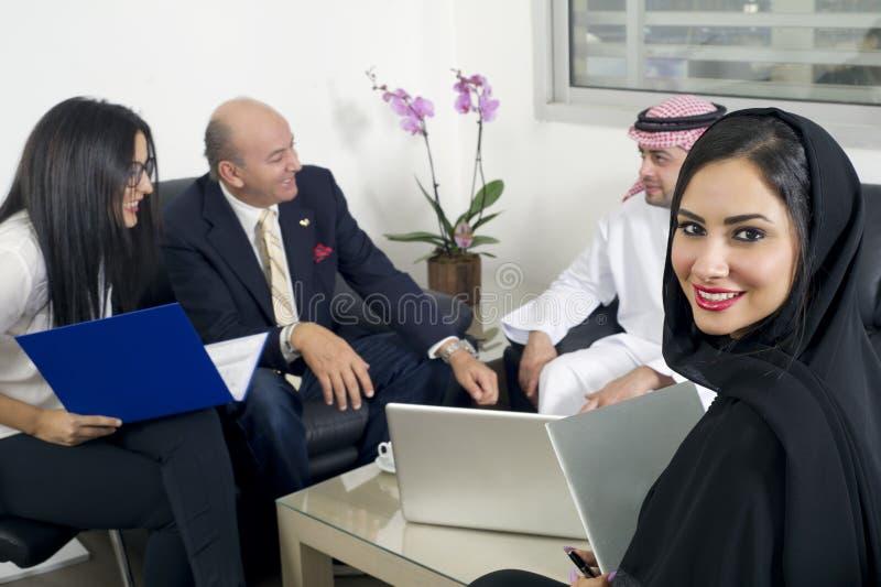 Arabische Onderneemster in bureau met Zakenlui die op de achtergrond samenkomen stock fotografie