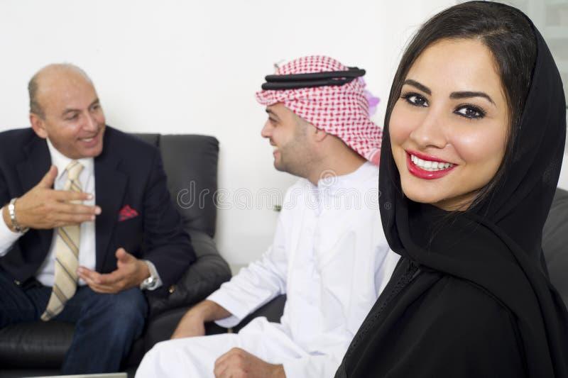 Arabische Onderneemster in bureau met Zakenlui die op de achtergrond samenkomen royalty-vrije stock fotografie