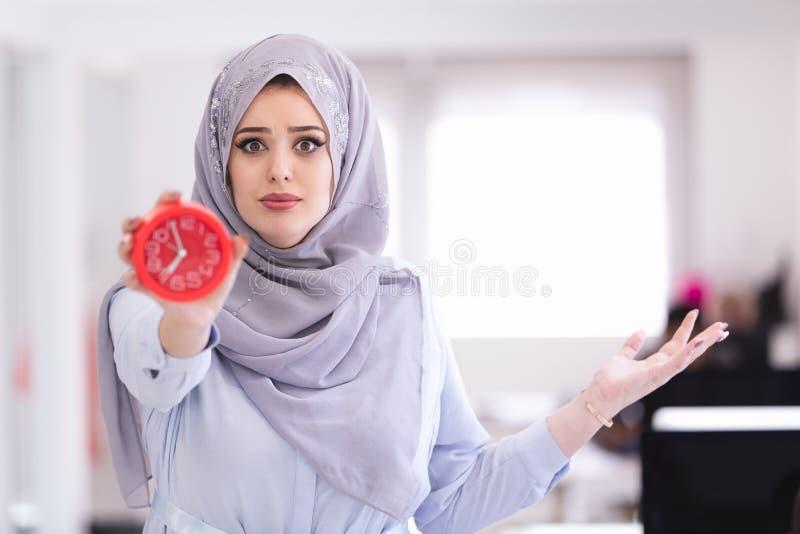 Arabische Onderneemster met klok die laat dragend hijab zijn royalty-vrije stock afbeeldingen