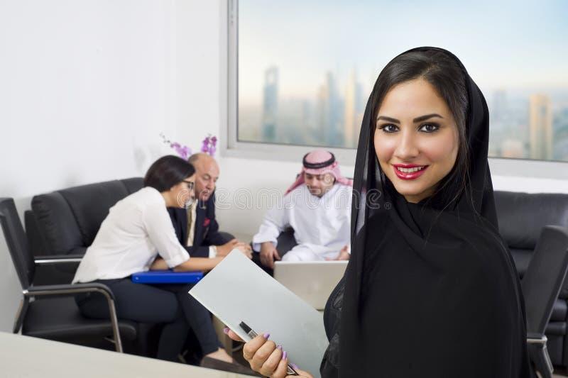 Arabische Onderneemster met Werknemers die op de achtergrond samenkomen royalty-vrije stock foto's
