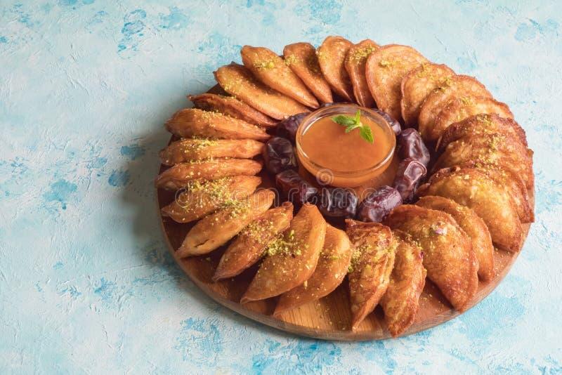 Arabische snoepjes De Arabische Qatayef-pannekoek vulde met zoete kaas en noten op de blauwe lijst stock foto
