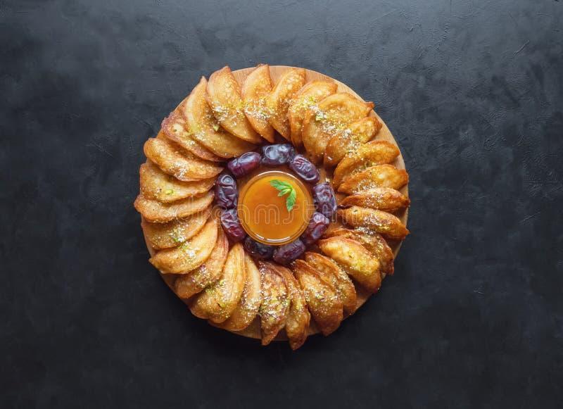Arabische snoepjes De Arabische Qatayef-pannekoek vulde met zoete kaas en noten op de zwarte lijst stock foto's