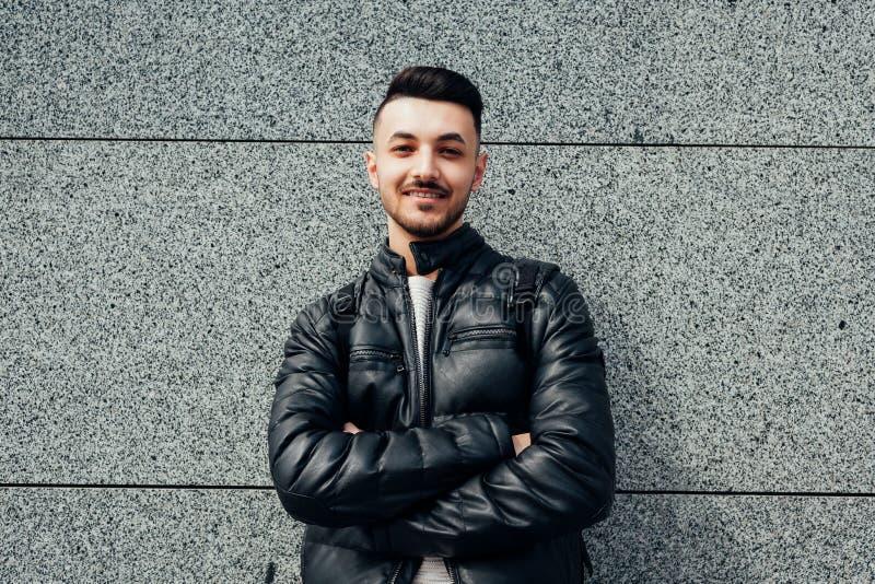 Arabische student met rugzak die door de muur zich buiten bevinden Jonge hipstermens die op groupmates wachten stock fotografie