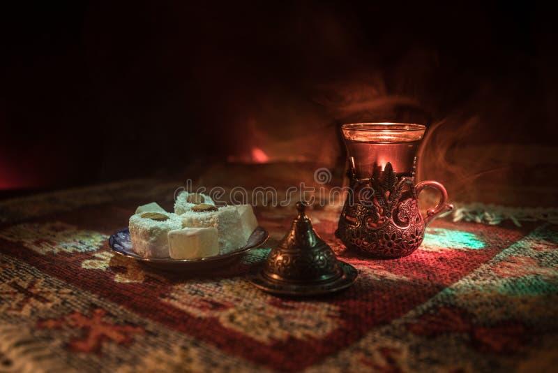 Arabische thee in glas met oostelijke snacks op een tapijt op donkere achtergrond met lichten en rook Oostelijk theeconcept Lege  stock foto's