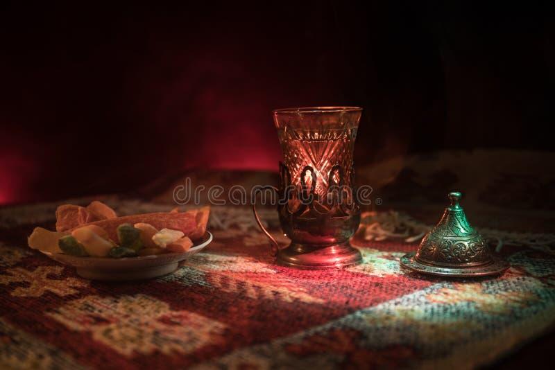 Arabische thee in glas met oostelijke snacks op een tapijt op donkere achtergrond met lichten en rook Oostelijk theeconcept Lege  royalty-vrije stock foto