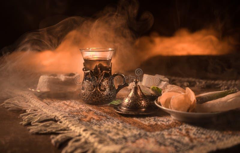 Arabische thee in glas met oostelijke snacks op een tapijt op donkere achtergrond met lichten en rook Oostelijk theeconcept Lege  royalty-vrije stock afbeelding