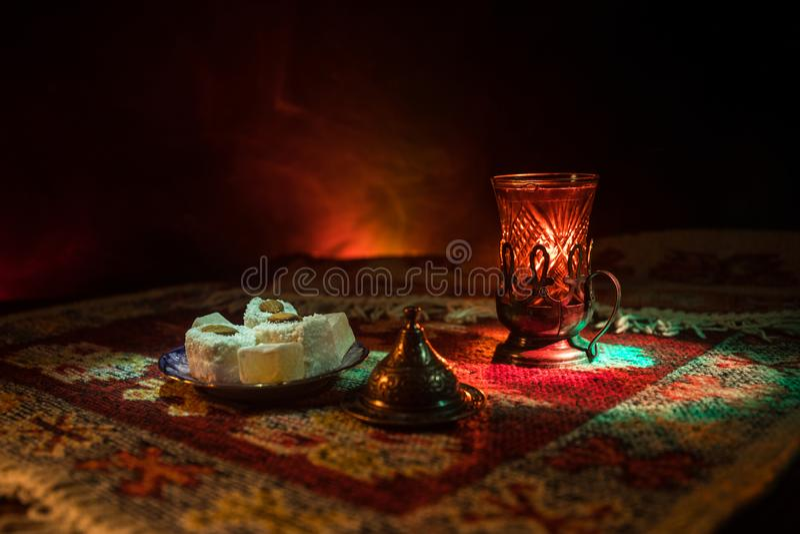 Arabische thee in glas met oostelijke snacks op een tapijt op donkere achtergrond met lichten en rook Oostelijk theeconcept Lege  royalty-vrije stock afbeeldingen