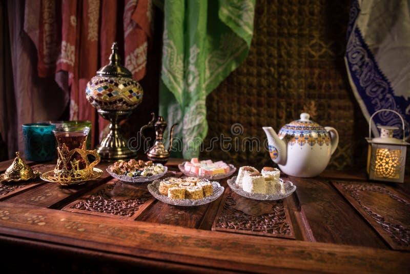 Arabische thee in glas met oostelijke snacks op uitstekende houten oppervlakte Oostelijk theeconcept Het binnenland van de laag l stock foto