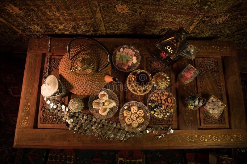 Arabische thee in glas met oostelijke snacks op uitstekende houten oppervlakte Oostelijk theeconcept Het binnenland van de laag l stock fotografie