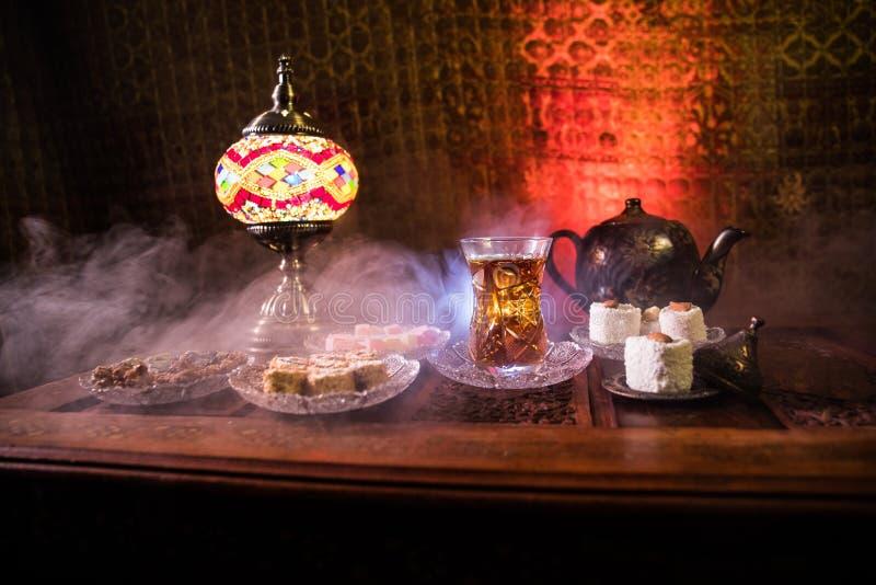 Arabische thee in glas met oostelijke snacks op uitstekende houten oppervlakte Oostelijk theeconcept Het binnenland van de laag l stock foto's