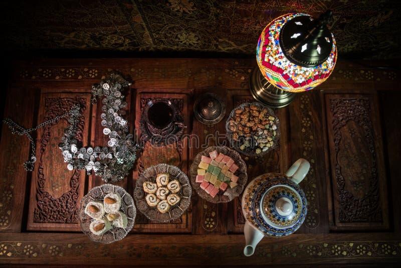 Arabische thee in glas met oostelijke snacks op uitstekende houten oppervlakte Oostelijk theeconcept Het binnenland van de laag l stock afbeeldingen