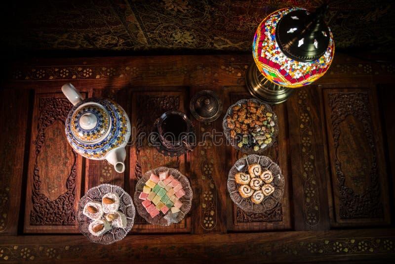 Arabische thee in glas met oostelijke snacks op uitstekende houten oppervlakte Oostelijk theeconcept Het binnenland van de laag l royalty-vrije stock foto's