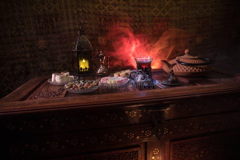 Arabische thee in glas met oostelijke snacks op uitstekende houten oppervlakte Oostelijk theeconcept Het binnenland van de laag l stock afbeelding