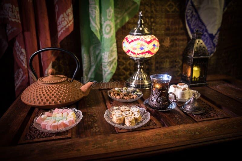 Arabische thee in glas met oostelijke snacks op uitstekende houten oppervlakte Oostelijk theeconcept Het binnenland van de laag l royalty-vrije stock afbeeldingen