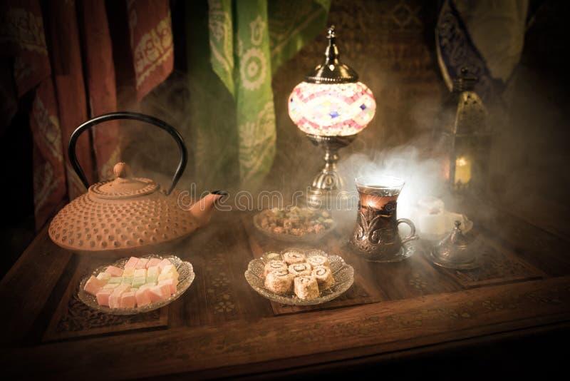 Arabische thee in glas met oostelijke snacks op uitstekende houten oppervlakte Oostelijk theeconcept Het binnenland van de laag l royalty-vrije stock afbeelding