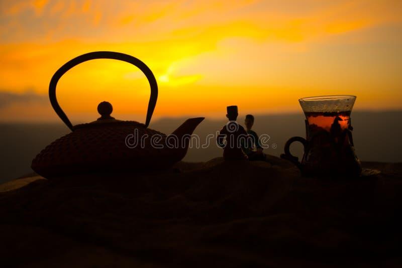 Arabische thee in traditioneel glas en pot op woestijn bij zonsondergang Oostelijk theeconcept Kunstwerkdecoratie op zand met the royalty-vrije stock foto's