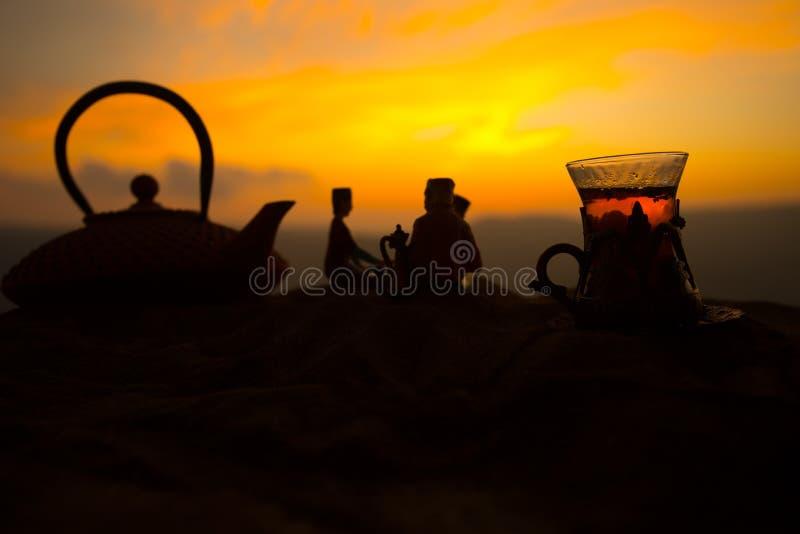 Arabische thee in traditioneel glas en pot op woestijn bij zonsondergang Oostelijk theeconcept Kunstwerkdecoratie op zand met the royalty-vrije stock afbeeldingen