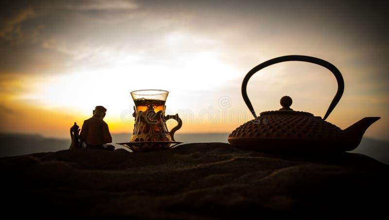 Arabische thee in traditioneel glas en pot op woestijn bij zonsondergang Oostelijk theeconcept Kunstwerkdecoratie op zand met the royalty-vrije stock fotografie