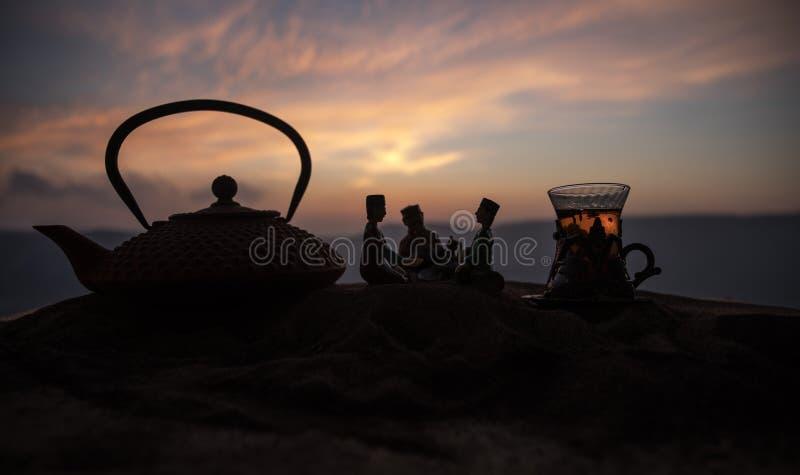 Arabische thee in traditioneel glas en pot op woestijn bij zonsondergang Oostelijk theeconcept Kunstwerkdecoratie op zand met the stock fotografie