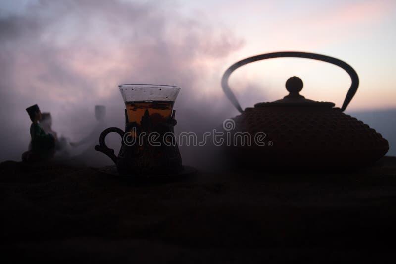 Arabische thee in traditioneel glas en pot op woestijn bij zonsondergang Oostelijk theeconcept Kunstwerkdecoratie op zand met the stock afbeeldingen