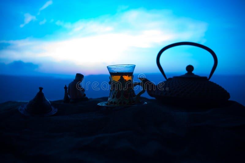 Arabische thee in traditioneel glas en pot op woestijn bij zonsondergang Oostelijk theeconcept Kunstwerkdecoratie op zand met the royalty-vrije stock afbeelding