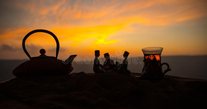 Arabische thee in traditioneel glas en pot op woestijn bij zonsondergang Oostelijk theeconcept Kunstwerkdecoratie op zand met the royalty-vrije stock foto