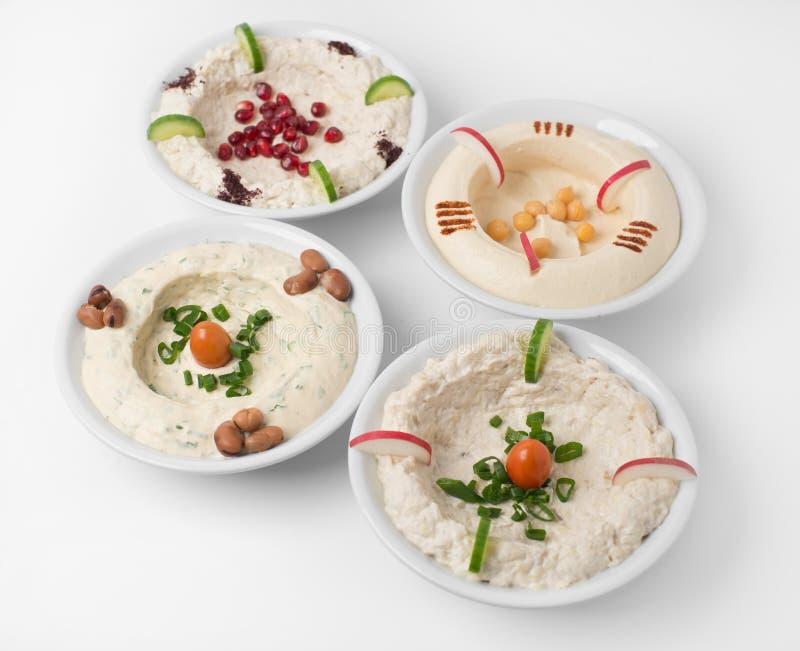 Arabische traditionelle Hummus-Platten mit verschiedenen Belägen stockbilder