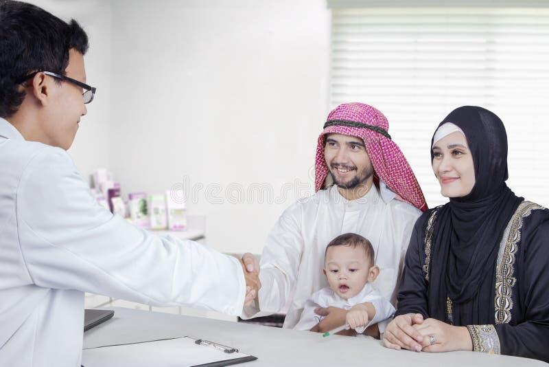 Arabische vader het schudden handen met arts royalty-vrije stock afbeelding