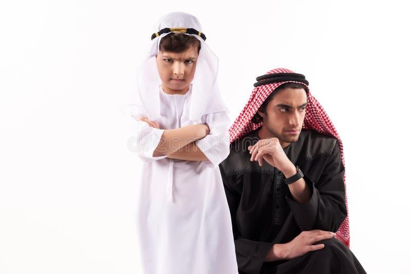 Arabische volwassen mens in keffiyeh in ruzie met zoon stock afbeelding