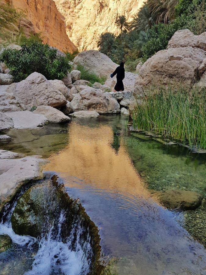 Arabische vrouw in de steenvallei die dichtbij duidelijke water en waterval lopen stock afbeelding