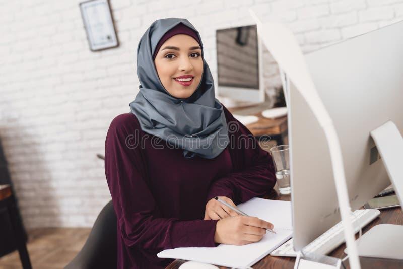 Arabische vrouw die in bureau werken De vrouwelijke werknemer neemt nota's bij lijst stock foto